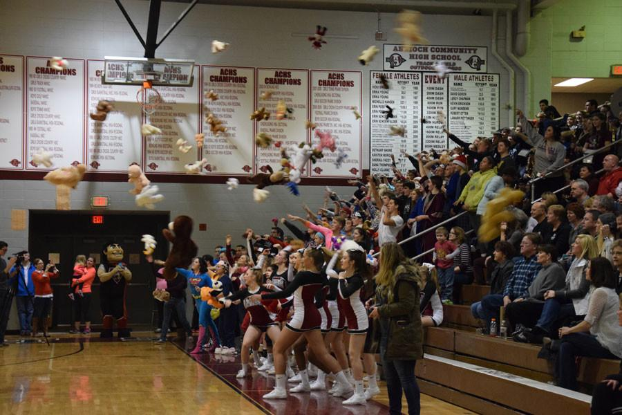 Students toss stuffed animals onto the court to donate for the special olympics.