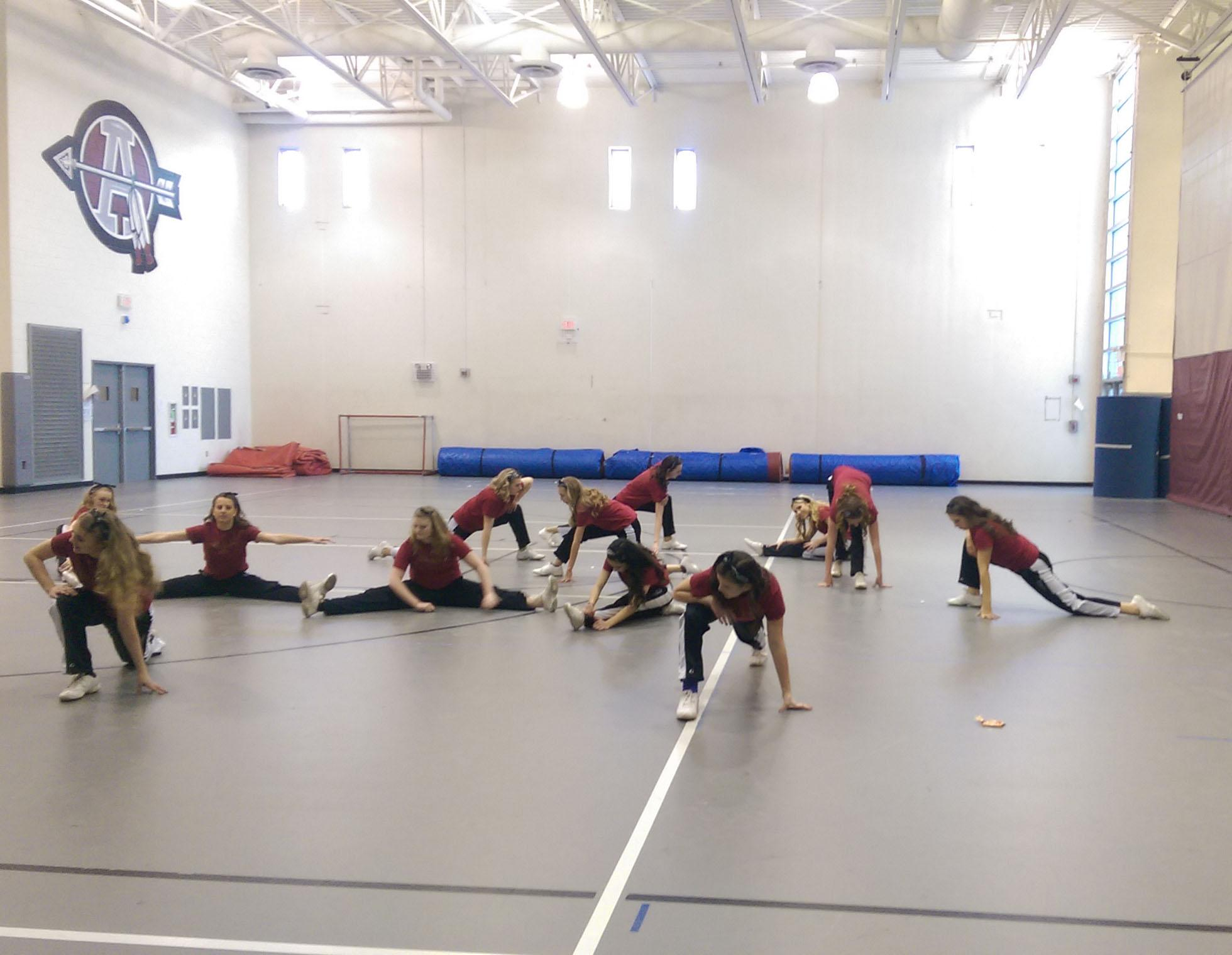 The Antioch varsity dance team stretches before their performance before the boys basketball game.