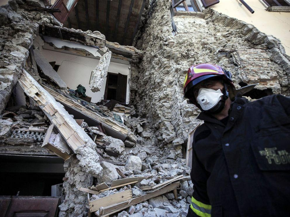 A firefighter walks past a collapsed house in Italy after Wednesday's earthquake.