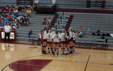 The volleyball girls gather for a timeout during the intense game.
