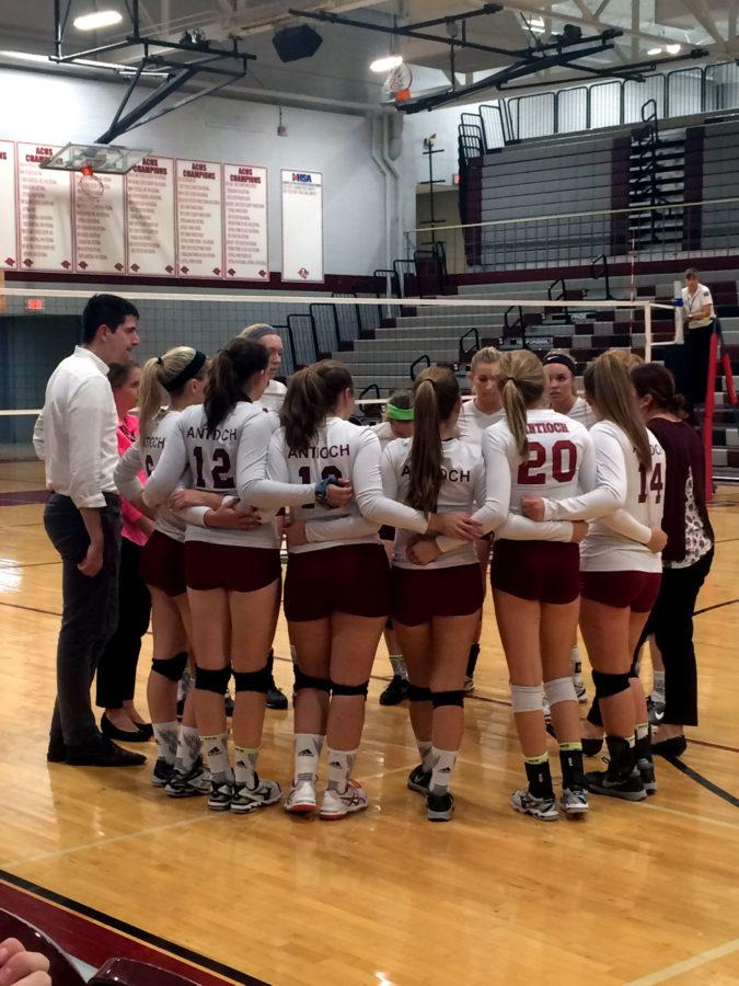 The girls Varsity volleyball gathers in a huddle to discuss their goals for the game.