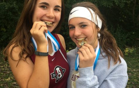 Sophomores Piper Foote and Megan Lawrence show off their medals after placing 2nd in their meet.