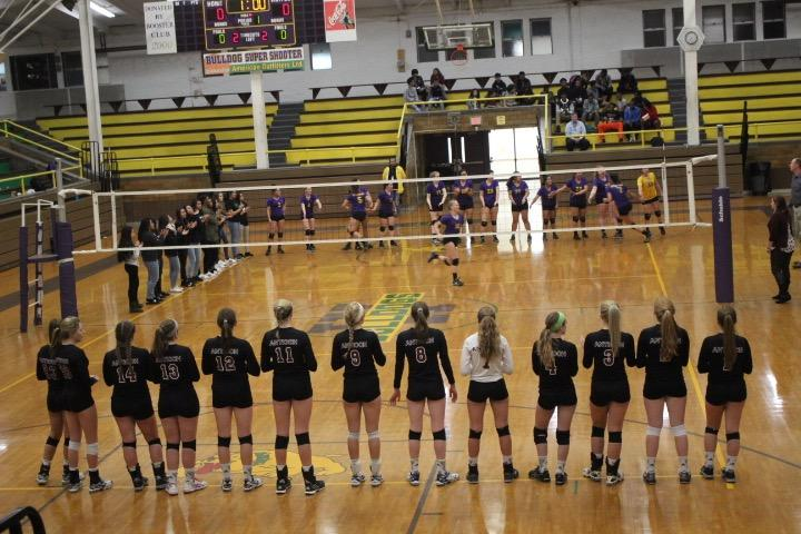 The+girls+volleyball+team+stands+for+the+introductions+of+both+teams+before+their+match+at+Waukegan.