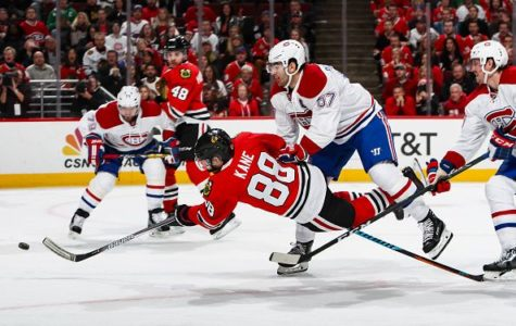 Patrick Kane shoots the puck while getting hit by Max Pacioretty