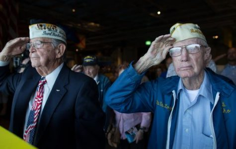 Two Pearl Harbor veterans stand and salute the flag during the moment of silence in remembrance of those who lost their lives in the 1941 attacks, which saw its 75th anniversary on Wednesday, December 7th.