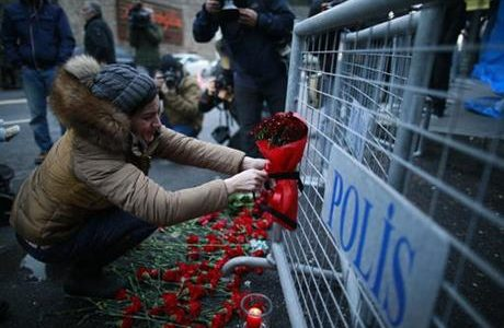 A young woman cries as she leaves flowers for the victims outside a nightclub which was attacked by a gunman overnight in Istanbul, Turkey on New Year's Day.