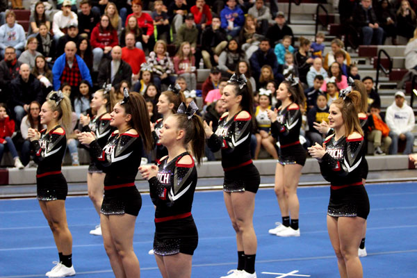 The cheer team performing for the conference championship at home.