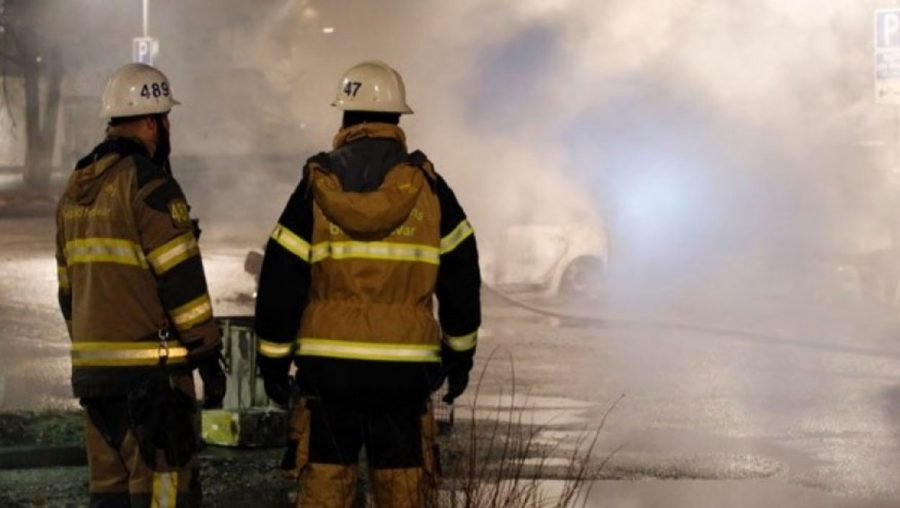 Firefighters in Stockholm, Sweden look upon the carcasses of two vehicles that were burned while riots raged on Sunday, Feb. 20.