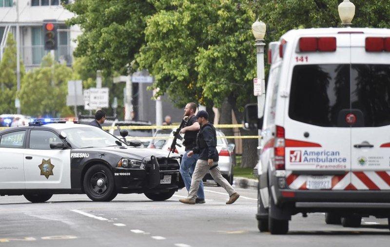 Fresno police members walk towards the scene of the shooting crime on Tuesday, April 18, 2017 in Fresno, California.