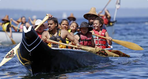 A canoe from the Puyallup Tribe is paddled toward a landing during an annual journey Wednesday, July 27, 2016, in Seattle. Dozens of tribal canoes were arriving at Alki Beach in Seattle as part of an annual Native American celebration. Members of the Muckleshoot Tribe greeted the boats Wednesday afternoon as part of the 2016 Paddle to Nisqually.