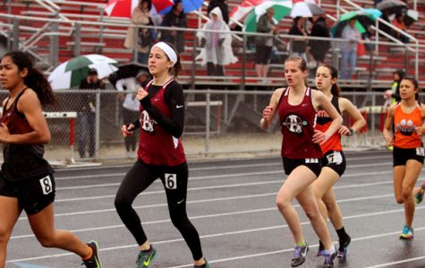 Senior Rylie Mercer and junior Allison Morris run the 3200 despite the rain. Mercer ran a personal best for this event in despite the weather.