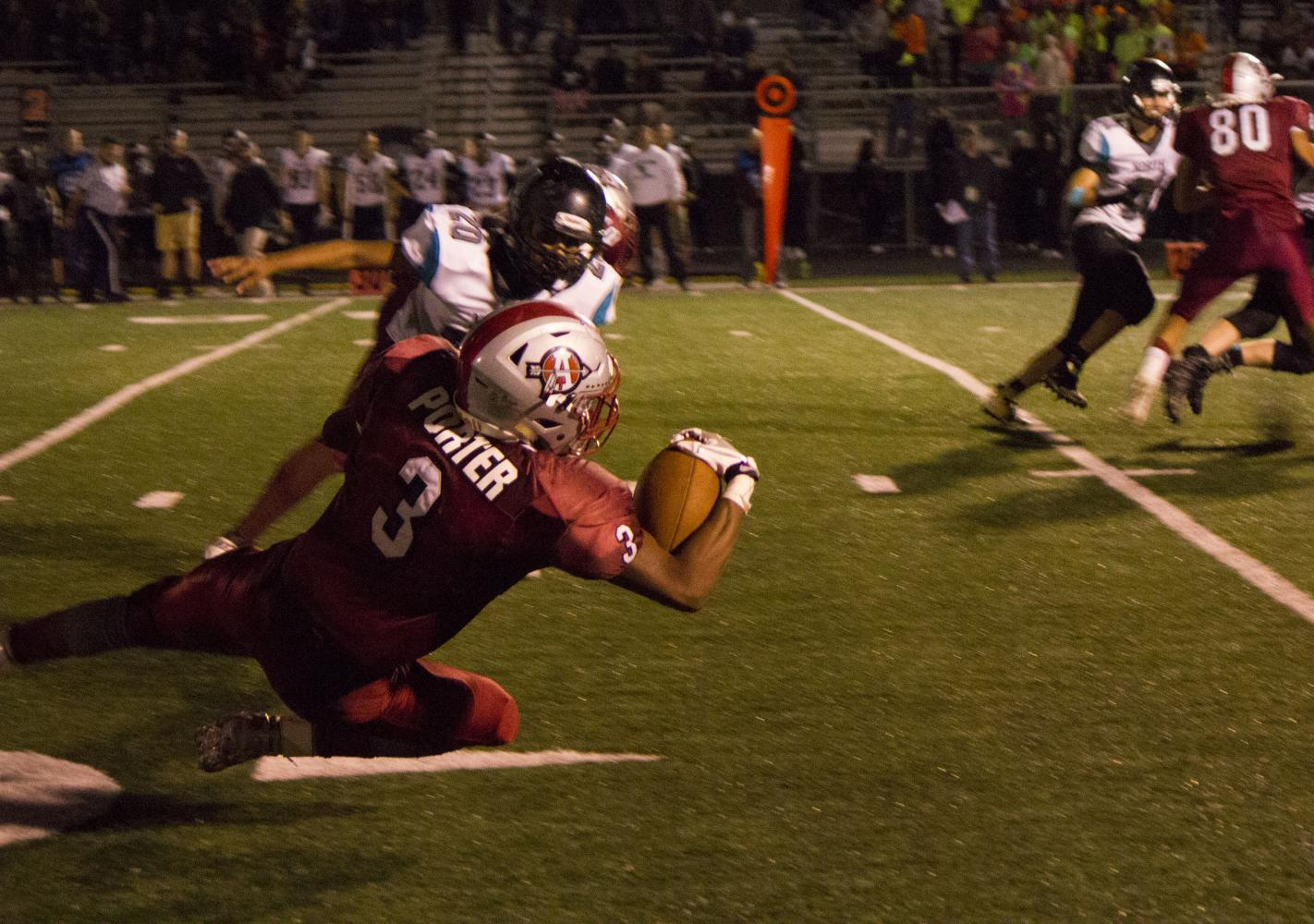 Senior Drew Porter falls to his knees to catch a pass in Friday night's game against Woodstock North.