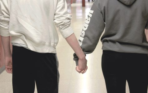 An ACHS couple holds hands in the hallway