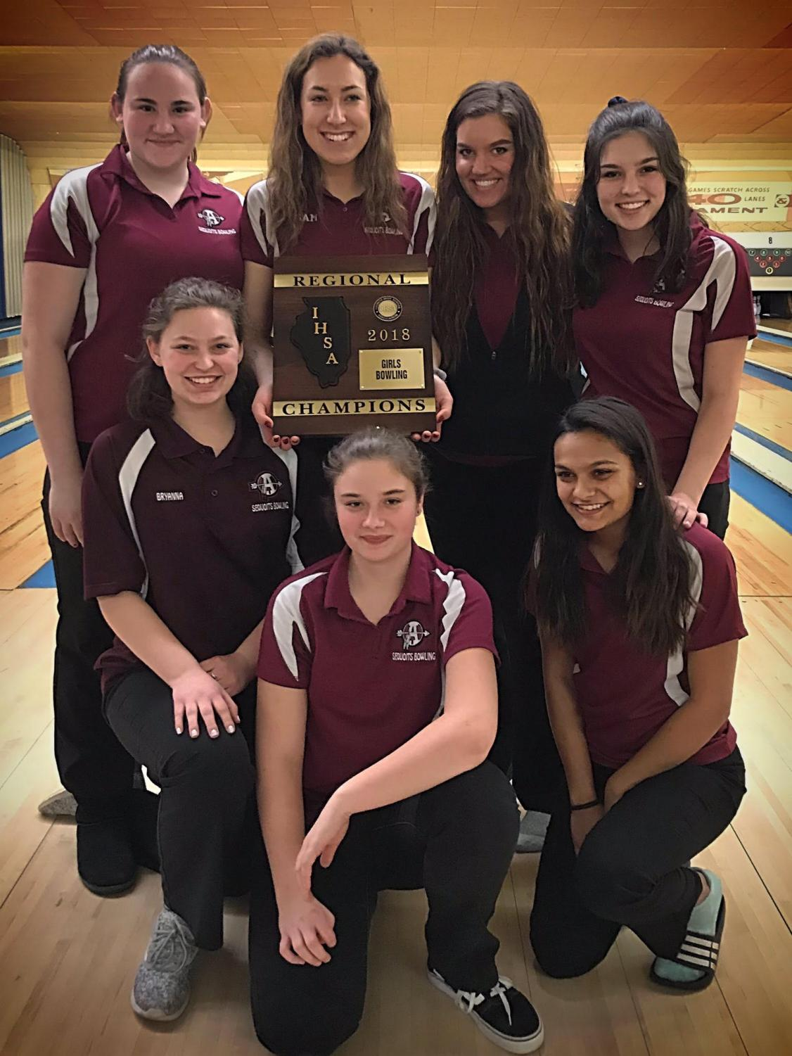 The bowling team shows off their regionals plaque.