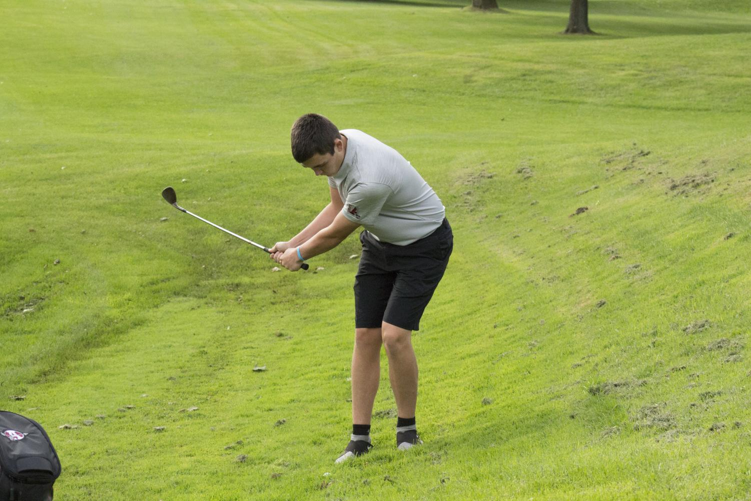 Gavin Eldridge, junior, chips the ball out of the rough, and down the fairway.