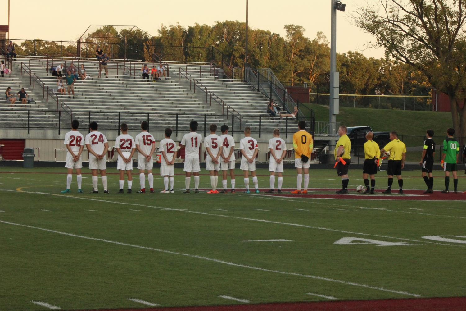 The boys varsity soccer team lines up to listen to the national anthem.