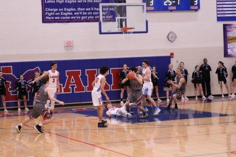 Senior Elias Vanderwagen looks to pass the ball as the Lakes defender takes a tumble.