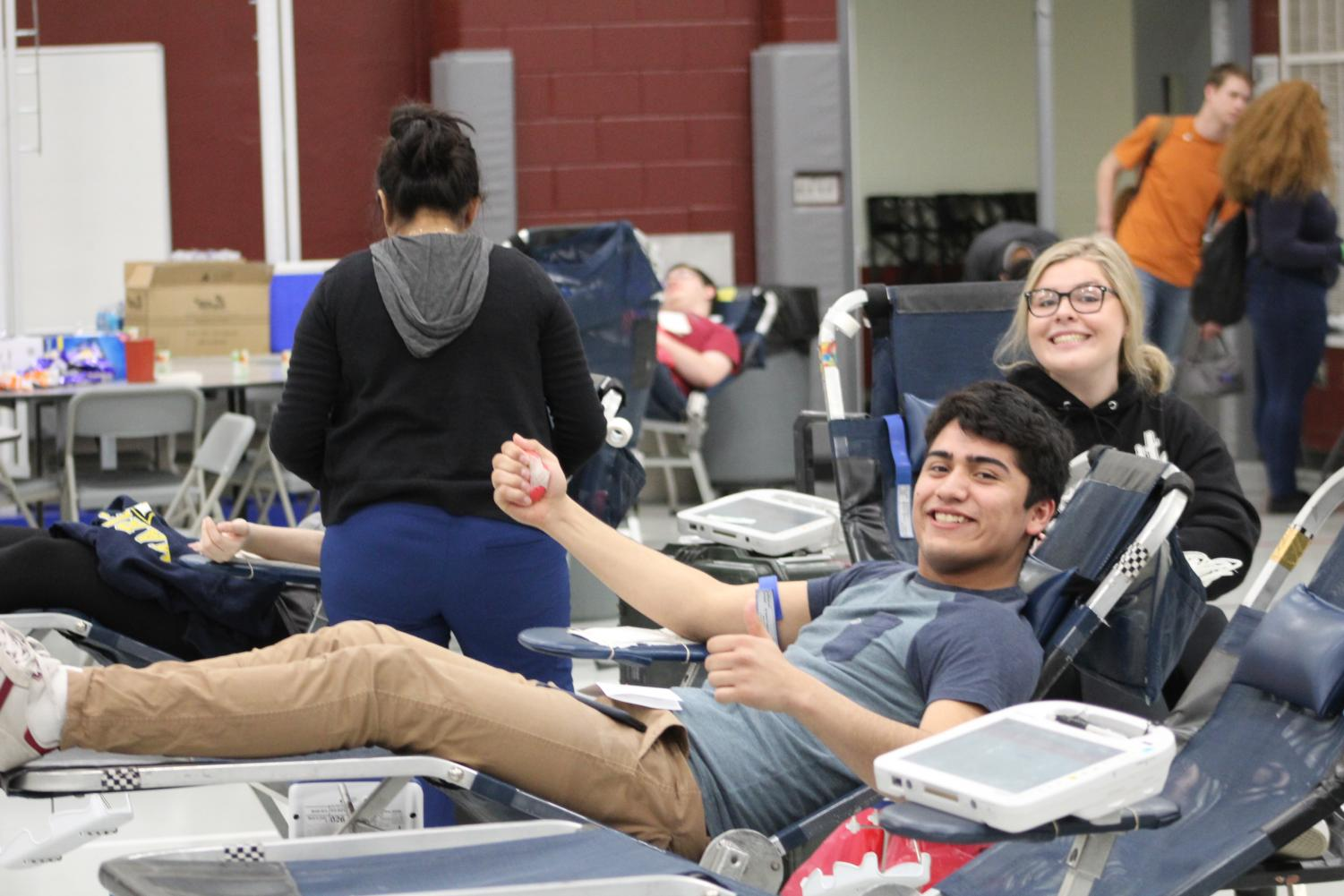 Seniors Christian Ortiz and Victoria Henkel smile as they donate blood.