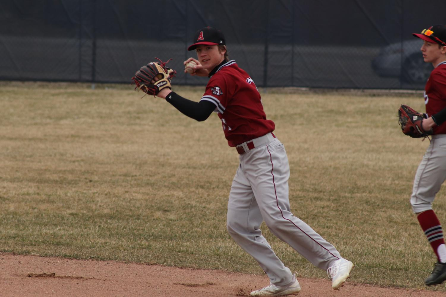 Sophomore Varsity Baseball player Ethan Andrews getting ready to throw the ball to get another out.
