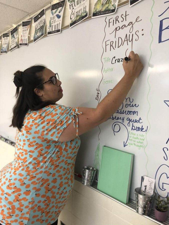 Teacher Amanda Cardenas writes the book title Crazy Love for her