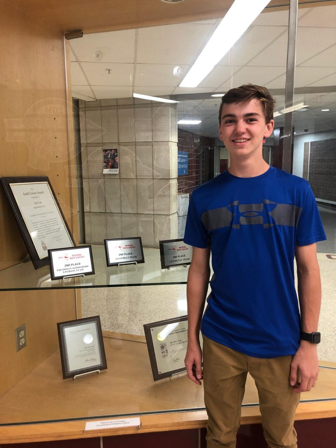Sophomore Jacob Slaboz stands proudly next to his math team's plaques from last year.