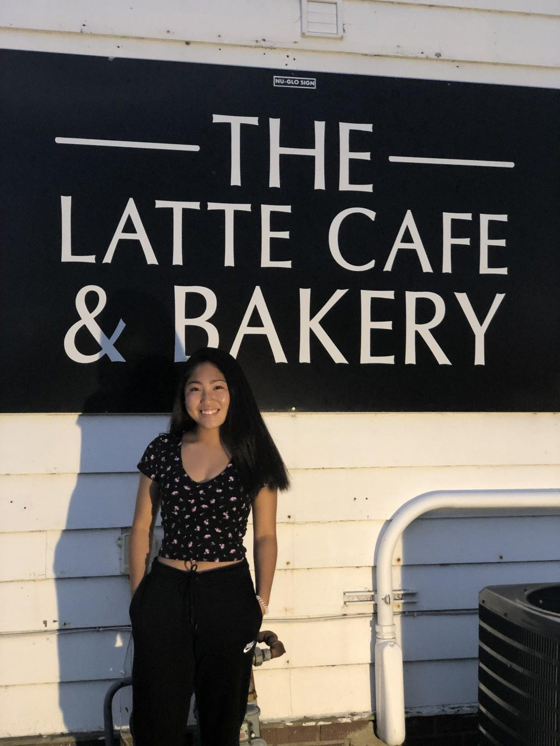 Coffee lover and enthusiast Olivia Lahti stands by the iconic Latte Cafe and Bakery sign in Antioch, Ill.