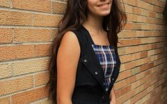 Sophomore Autumn RIzzo is wearing a black jumpsuit with a plaid tank top.
