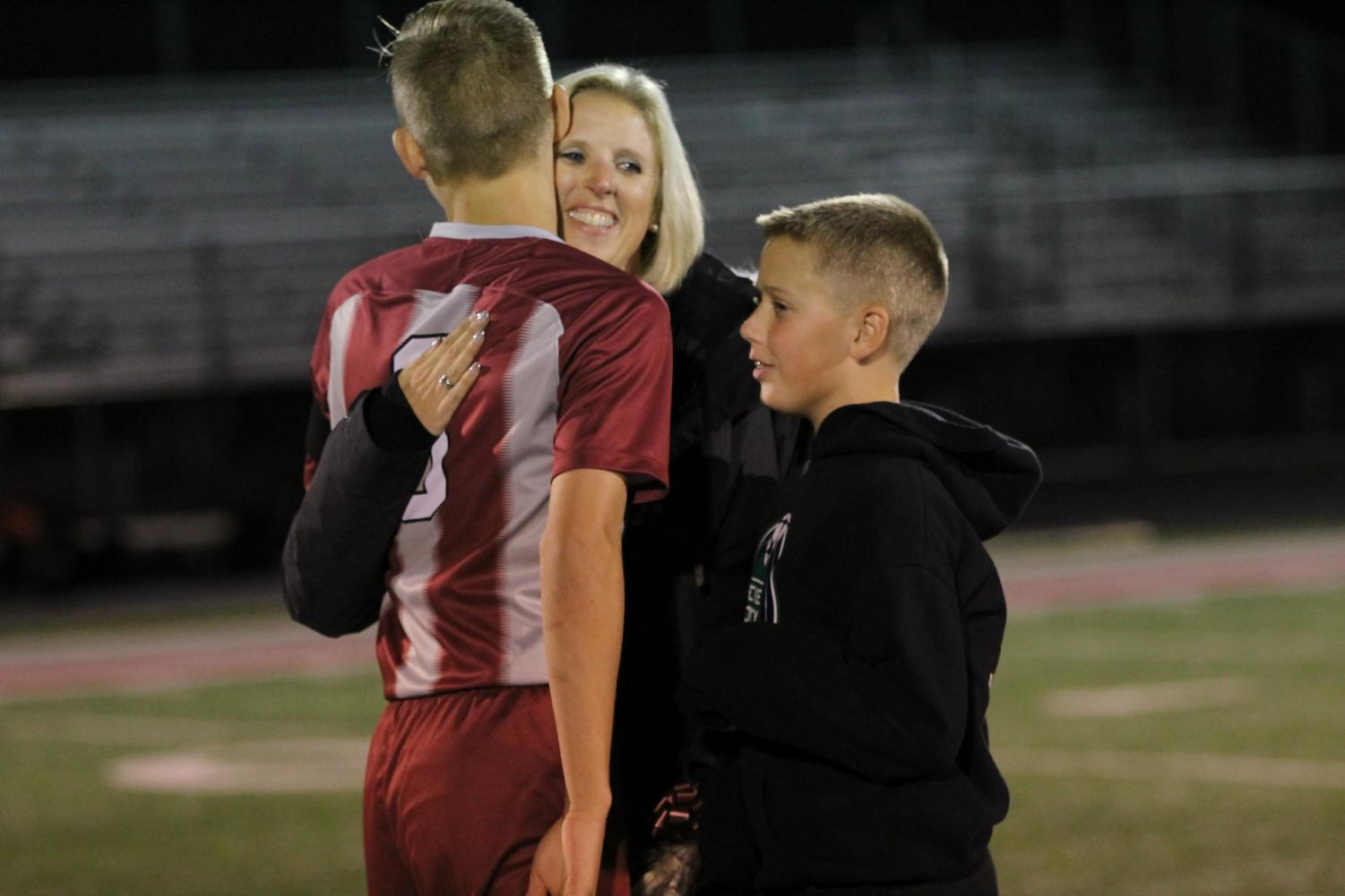 Senior captain Adam Lynn hugs his mom on senior night.