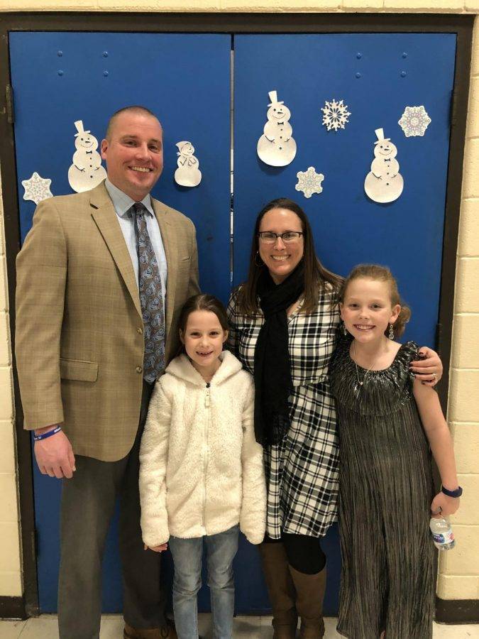 New District 34 superintendent Bradford Hubbard stands with his wife and children at the board meeting to celebrate his new beginnings.