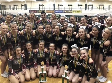 Junior varsity and varsity take a group picture with their first place trophies that they won at the Fremd cheer competition.