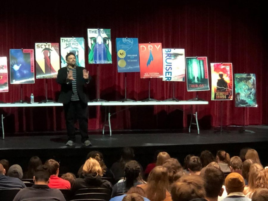"Pictured are Shusterman and his assorted works. From left to right, they are: ""The Shadow Club"", ""Full Tilt"", ""Unwind"", ""Scythe"", ""Thunder Head"", ""The Tull"", ""Challenger Deep"", ""Dry"", ""Bruiser"", ""Everlost"", ""Scorpion Shards"" and ""Tesla"