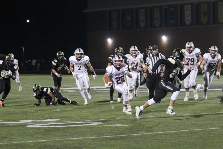 Senior Renio Hill runs the ball for a gain of multiple yards to help the Sequoits move closer to the end zone.